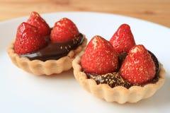 Mouthwatering une paire de tartes de chocolat complétées avec les fraises fraîches et de poudre comestible d'or a servi du plat b photo libre de droits