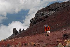Moutnain climbing. Hiker at an altitude above the clouds when ascending to climb Mount Fuji in Japan Stock Photos