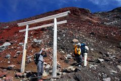 Moutnain climbing. Hikers at an altitude above the clouds when ascending to climb Mount Fuji in Japan passing a shinto torii along the path Royalty Free Stock Images