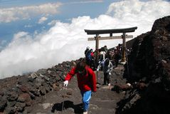 Moutnain climbing. Hikers at an altitude above the clouds when ascending to climb Mount Fuji in Japan passing a shinto torii along the path Stock Photos