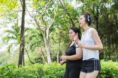Mouvement brouillé de grosse femme et d'exercice mince de femme en pulsant en parc, ils fonctionnent pour la santé photographie stock