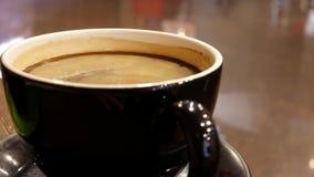 Mouvement de café chaud avec des bulles sur la table et la réflexion avec des personnes marchant  banque de vidéos