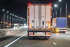 Mouvement de camions sur une autoroute de nuit Images libres de droits