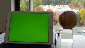 Mouvement de comprimé vert d'écran et de globe de rotation sur la table clips vidéos