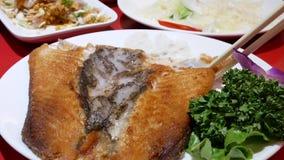 Mouvement de femme mangeant les poissons et le légume cuits à la friteuse à l'intérieur du restaurant chinois banque de vidéos