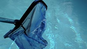Mouvement de filet de nettoyage de piscine sur l'eau avec des ondulations banque de vidéos