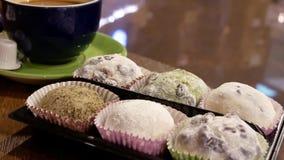Mouvement de gâteau de café chaud et de riz collant sur la table avec le fond de réflexion des personnes marchant  banque de vidéos