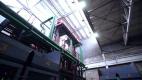 Mouvement de tir d'angle faible le long d'atelier d'usine avec des canalisations banque de vidéos