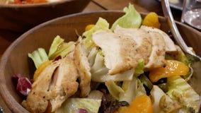 Mouvement des personnes mangeant de la salade grillée d'agrume de poulet sur la table banque de vidéos