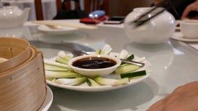 Mouvement des personnes mangeant l'oignon vert sur la table à l'intérieur du restaurant chinois banque de vidéos