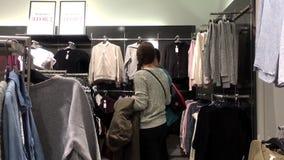 Mouvement des vêtements de achat de client et rivaliser avec un autre banque de vidéos