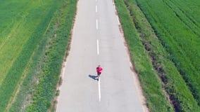 Mouvement lent aérien : le bourdon dépistant l'homme seul courant sur le croisement de route de campagne a cultivé des champs, fo banque de vidéos