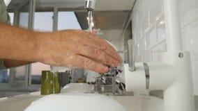 Mouvement lent avec un homme à la maison lavant des plats dans l'évier avec le jet d'eau clair clips vidéos