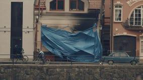 Mouvement lent : Bâche aveugle la façade du bâtiment après un feu rideau banque de vidéos
