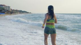 Mouvement lent, belle femme bronzée courant sur les vagues sur la plage de mer pendant le matin clips vidéos