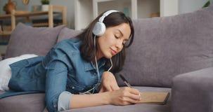 Mouvement lent d'image de dessin et d'écouter de jeune dame la musique dans des écouteurs clips vidéos
