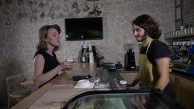 Mouvement lent d'un café masculin de portion de barman à aller tandis que le client féminin paye utilisant son smartphone et lais banque de vidéos