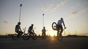 Mouvement lent de cycliste frais montant sa bicyclette utilisant la roue avant et un pied à la terre devant des cyclistes banque de vidéos