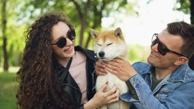 Mouvement lent de deux propriétaires de soin de chien de personnes embrassant et tapotant l'animal familier de pure race adorable clips vidéos