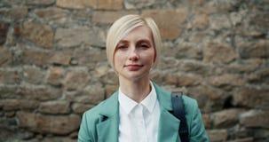 Mouvement lent de femme d'affaires attirante se tenant dehors avec le visage sérieux banque de vidéos