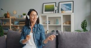 Mouvement lent de fille dans des écouteurs dansant écouter la musique se reposant sur le sofa clips vidéos