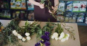 Mouvement lent de fleuriste féminin tenant de belles fleurs faisant le bouquet dans le magasin banque de vidéos
