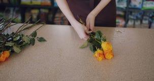 Mouvement lent de fleuriste faisant le bouquet des roses lumineuses travaillant dans le fleuriste banque de vidéos