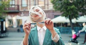 Mouvement lent de hippie joyeux enlevant des lunettes de soleil se tenant dans le sourire de rue banque de vidéos