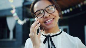 Mouvement lent de l'adolescent joyeux de métis parlant au téléphone portable dehors banque de vidéos