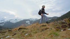 Mouvement lent de l'homme escaladant la montagne avec le nordic Polonais de marche en hiver clips vidéos