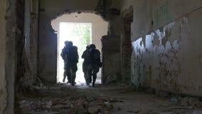 Mouvement lent de l'unité spéciale d'infiltration marchant à une entrée d'un bâtiment abandonné tout en recherchant l'ennemi banque de vidéos