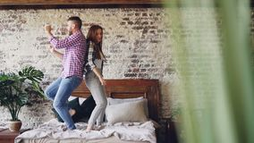Mouvement lent de la jeune belle et affectueuse danse de couples ayant l'amusement et riant dans le lit à la maison Inattention,  clips vidéos