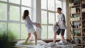 Mouvement lent de mari heureux et d'épouse de couples ayant le combat d'oreiller sur le double lit, ayant l'amusement et rire Les banque de vidéos