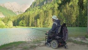 Mouvement lent de pêcheur handicapé dans un fauteuil roulant électrique pêchant en beau lac près de la forêt et montagne dans banque de vidéos