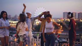 Mouvement lent de partie en retard de dessus de toit avec les personnes joyeuses dansant s'appréciant et le disc-jockey masculin  banque de vidéos