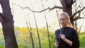 Mouvement lent de Steadicam tiré : Une jeune femme attirante fait un essai de matin dans la forêt que le soleil est brillant admi clips vidéos
