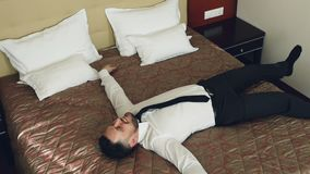Mouvement lent de vue supérieure d'homme d'affaires heureux sautant sur le lit à la chambre d'hôtel et au sourire décontracté men clips vidéos