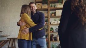 Mouvement lent des acheteurs d'immobiliers obtenant des clés de l'agent immobilier après affaire réussie, les embrassant et étrei banque de vidéos