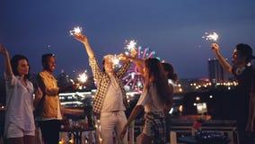 Mouvement lent des amis heureux brûlant des lumières de Bengale et dansant sur le dessus de toit célébrant des vacances ensemble  banque de vidéos