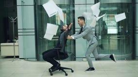 Mouvement lent des associés heureux ayant l'amusement dans la chaise d'équitation de bureau et jetant des contrats de papiers app banque de vidéos