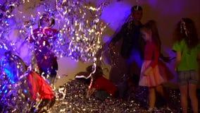 Mouvement lent des enfants gais jetant les colifichets argentés de scintillement banque de vidéos