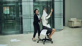Mouvement lent des femmes d'affaires enthousiastes tourbillonnant en chaise de roulement et journal de lancement en air, riant et banque de vidéos