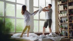 Mouvement lent des jeunes enthousiastes ayant le combat d'oreiller sur le double lit, ils ont l'amusement sautant et riant heureu clips vidéos