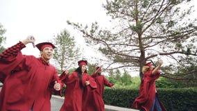 Mouvement lent des joyeux et émotifs jeunes courant avec des diplômes portant des mortier-conseils et des robes ondulant des roul banque de vidéos