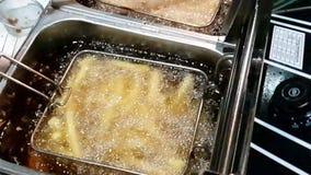 Mouvement lent des pommes frites faisant frire dans le restaurant clips vidéos