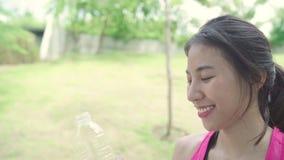 Mouvement lent - eau potable de belle jeune femme asiatique en bonne santé de coureur parce que la sensation a fatigué après fonc banque de vidéos