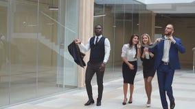 Mouvement lent Exulter positif sûr d'hommes d'affaires de groupe du gain Gens d'affaires marchant le long du couloir de bureau banque de vidéos