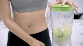 Mouvement lent - femme asiatique sportive à l'aide du mélangeur pour faire le jus de pomme dans la cuisine clips vidéos
