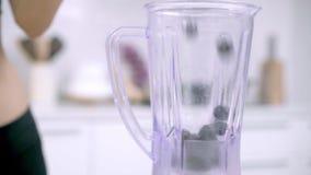 Mouvement lent - femme asiatique sportive à l'aide du mélangeur pour faire le jus de raisins dans la cuisine banque de vidéos