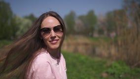 MOUVEMENT LENT 120fps : Fille d'une chevelure de femme de jeune brun heureux de voyageur souriant et tournant autour dans un nouv banque de vidéos